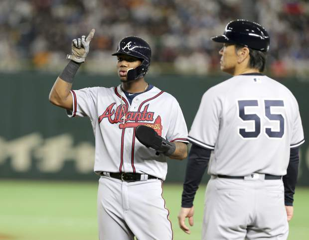 MLB All-Star Ronald Acuna Jr. of the Atlanta Braves points to the ceiling while talking with first base coach Hideki Matsui (55) after teammate Juan Soto of the Washington Nationals ground-rule flied out in the fourth inning of Game 3 against All Japan at the All-Stars Series baseball at Tokyo Dome in Tokyo, Sunday, Nov. 11, 2018. (AP Photo/Toru Takahashi)