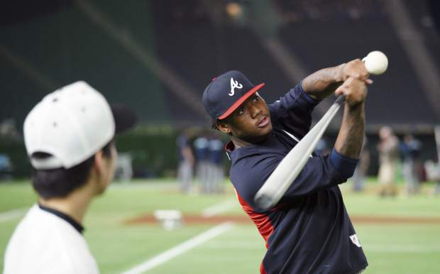 MLB All-Star Atlanta Braves' Ronald Acuna Jr. hits a ball to Japanese junior high school students during MLB All Stars Baseball clinic as part of All-Stars Series baseball games at Tokyo Dome in Tokyo Saturday, Nov. 10, 2018. (AP Photo/Eugene Hoshiko)