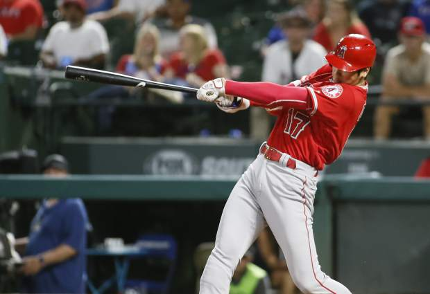 FILE - In this Sept. 5, 2018, file photo, Los Angeles Angels' Shohei Ohtani follows through on a two-run home run against the Texas Rangers during the eighth inning of a baseball game in Arlington, Texas. Ohtani is a finalist against two New York Yankees teammates for the AL Rookie of the Year award. The Baseball Writers' Association of America revealed the finalists for its major awards Monday, Nov. 5, 2018. (AP Photo/Ray Carlin, File)