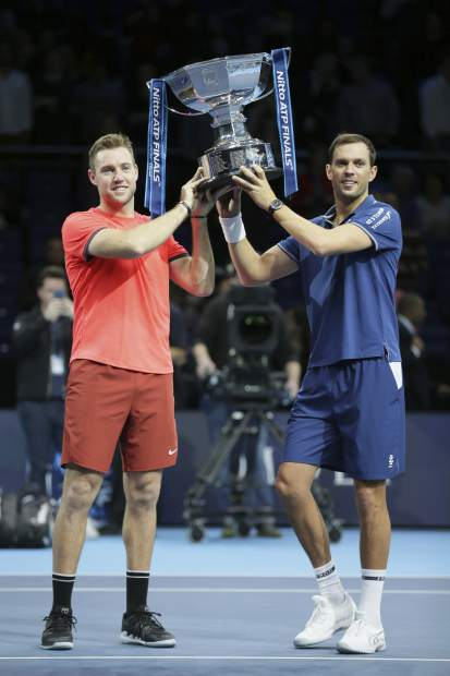 Mike Bryan, right, and Jack Sock of the United States hold up their trophy after defeating Pierre-Hugues Herbert and Nicolas Mahut of France during their ATP World Tour Finals doubles final tennis match at the O2 Arena in London, Sunday Nov. 18, 2018. (AP Photo/Tim Ireland)