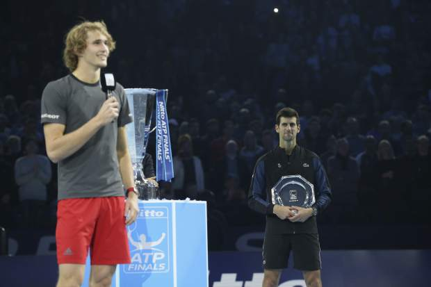 Novak Djokovic of Serbia holds his runner-up trophy as Alexander Zverev of Germany speaks to the crowds after their ATP World Tour Finals singles final tennis match at the O2 Arena in London, Sunday Nov. 18, 2018. (AP Photo/Tim Ireland)