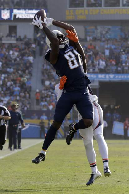 Los Angeles Chargers wide receiver Mike Williams catches a pass over Denver Broncos defensive back Tramaine Brock. during the first half of an NFL football game Sunday, Nov. 18, 2018, in Carson, Calif. (AP Photo/Marcio Jose Sanchez)