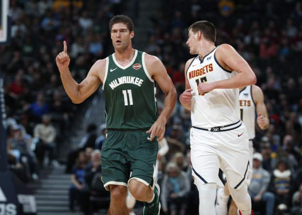 Milwaukee Bucks center Brook Lopez, left, gestures after hitting a three-point-basket over Denver Nuggets center Nikola Jokic in the first half of an NBA basketball game Sunday, Nov. 11, 2018, in Denver. (AP Photo/David Zalubowski)