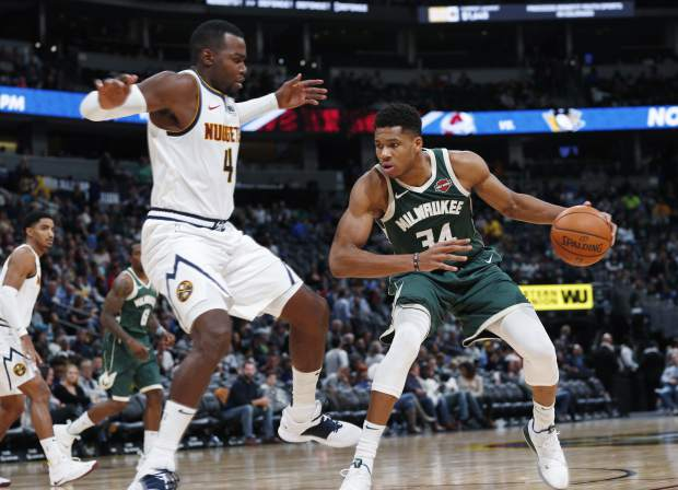 Milwaukee Bucks forward Giannis Antetokounmpo, right, drives the lane as Denver Nuggets forward Paul Millsap defends in the second half of an NBA basketball game Sunday, Nov. 11, 2018, in Denver. Milwaukee won 121-114. (AP Photo/David Zalubowski)