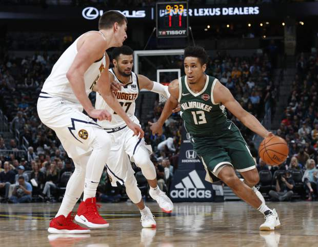 Milwaukee Bucks guard Malcolm Brogdon, right, drives to the rim past Denver Nuggets center Nikola Jokic, front left, and guard Jamal Murray in the second half of an NBA basketball game Sunday, Nov. 11, 2018, in Denver. Milwaukee won 121-114. (AP Photo/David Zalubowski)