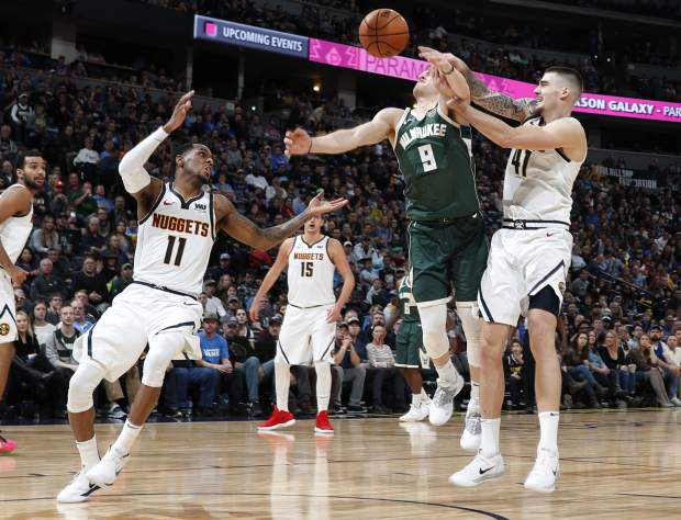 Milwaukee Bucks guard Donte DiVincenzo, center, loses the ball as he drives the lane between Denver Nuggets guard Monte Morris, left, and forward Juan Hernangomez in the second half of an NBA basketball game Sunday, Nov. 11, 2018, in Denver. Milwaukee won 121-114. (AP Photo/David Zalubowski)