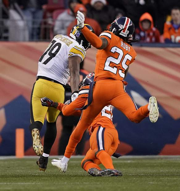 Pittsburgh Steelers wide receiver JuJu Smith-Schuster (19) breaks free for a touchdown as Denver Broncos cornerback Bradley Roby (29) and strong safety Darian Stewart pursue during the first half of an NFL football game, Sunday, Nov. 25, 2018, in Denver. (AP Photo/Jack Dempsey)