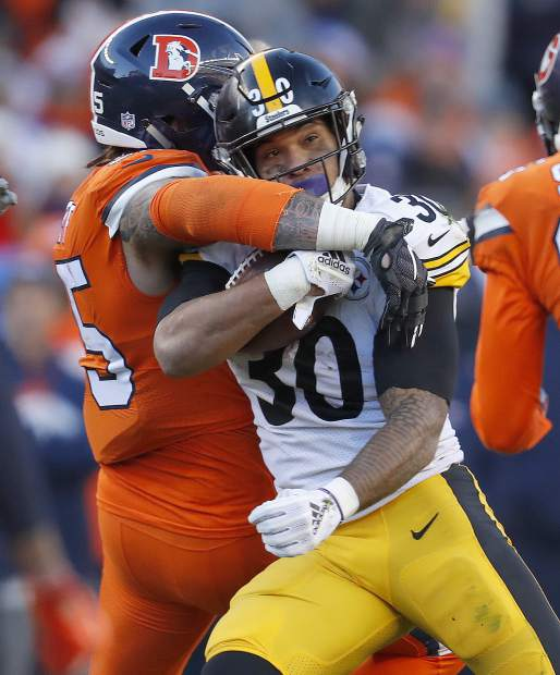 Pittsburgh Steelers running back James Conner (30) is hit by Denver Broncos outside linebacker Bradley Chubb (55) during the first half of an NFL football game, Sunday, Nov. 25, 2018, in Denver. (AP Photo/David Zalubowski)