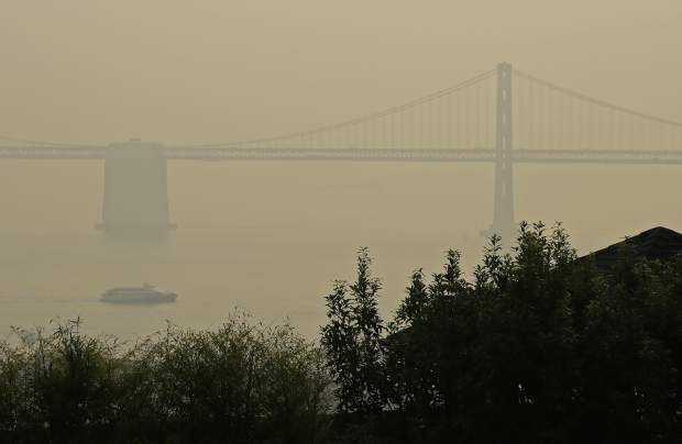 A ferryboat and the San Francisco-Oakland Bay Bridge are obscured due to smoke and haze from wildfires Monday, Nov. 19, 2018, in San Francisco. (AP Photo/Eric Risberg)