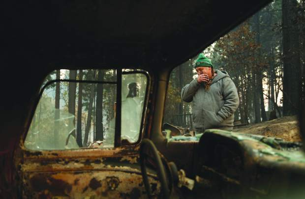 In this Nov. 15, 2018, photo, Troy Miller wipes his eyes as he walks beside a burned out car on his property in Concow, Calif. Miller said he tried to evacuate when the Camp Fire came roaring through the area, but had to turn back when the roads were blocked with debris and fire. A small group of residents who survived the deadly wildfire are defying evacuation orders and living in the burn zone. (AP Photo/John Locher)