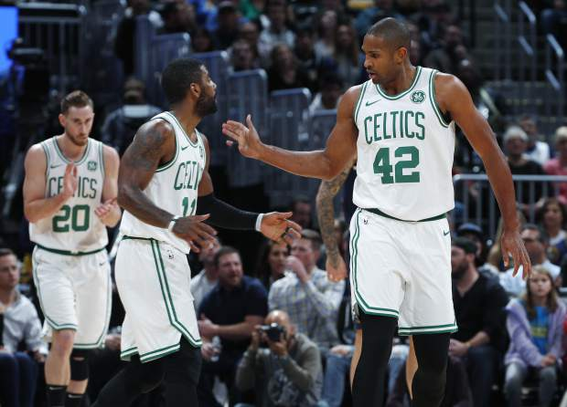 Boston Celtics guard Kyrie Irving, left, congratulates center Al Horford after his basket against the Denver Nuggets in the first half of an NBA basketball game Monday, Nov. 5, 2018, in Denver. (AP Photo/David Zalubowski)