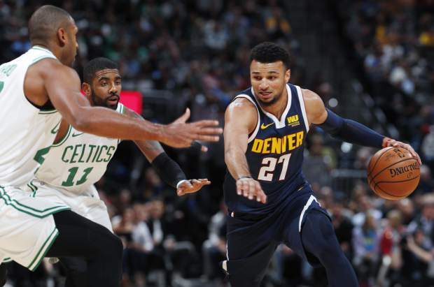 Denver Nuggets guard Jamal Murray, right, drives the lane as Boston Celtics center Al Horford, left, and guard Kyrie Irving, center, defend in the first half of an NBA basketball game Monday, Nov. 5, 2018, in Denver. (AP Photo/David Zalubowski)