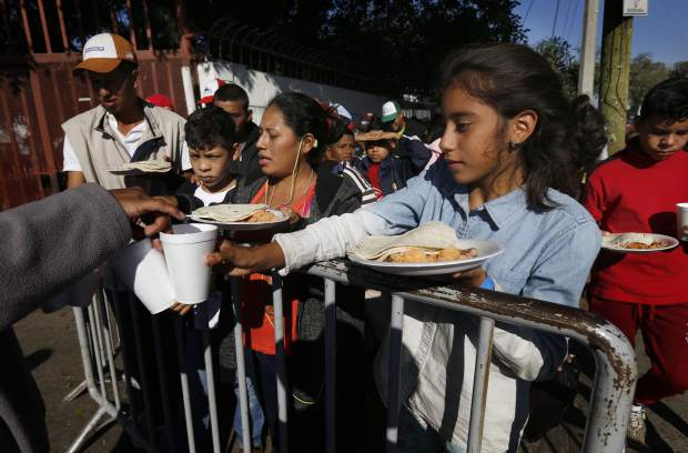 Central American migrants eat a free breakfast outside a shelter for migrants in Tijuana, Sunday, Nov. 18, 2018. While many in Tijuana are sympathetic to the plight of Central American migrants and trying to assist, some locals have shouted insults, hurled rocks and even thrown punches at the migrants. (AP Photo/Marco Ugarte)