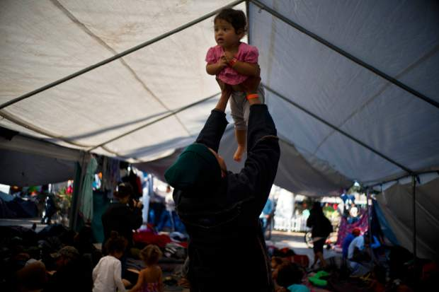 Cesar Elvir, a migrant from Honduras, lifts his daughter Sujhey at a migrant shelter in Tijuana, Mexico, Sunday, Nov. 18, 2018. While many in Tijuana are sympathetic to the plight of Central American migrants and trying to assist, some locals have shouted insults, hurled rocks and even thrown punches at the migrants. (AP Photo/Ramon Espinosa)
