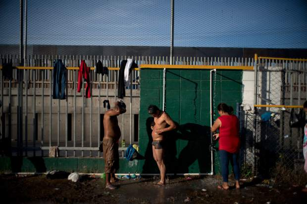 Central American migrants shower at a shelter in Tijuana, Mexico, Sunday, Nov. 18, 2018. While many in Tijuana are sympathetic to the plight of Central American migrants and trying to assist, some locals have shouted insults, hurled rocks and even thrown punches at the migrants. (AP Photo/Ramon Espinosa)