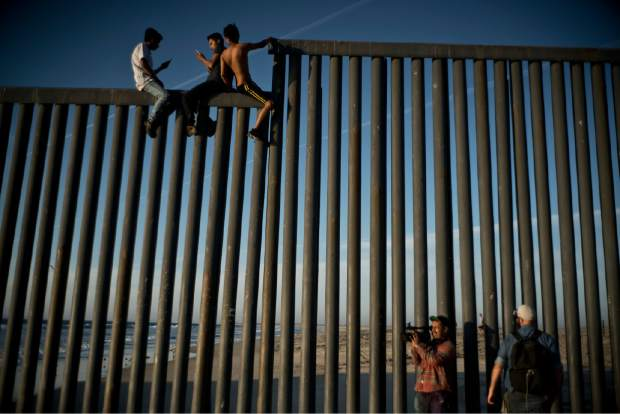Mexican citizens climb the border fence to take pictures of themselves on top of the structure, in Tijuana, Mexico, Sunday, Nov. 18, 2018. While many in Tijuana are sympathetic to the plight of Central American migrants and trying to assist, some locals have shouted insults, hurled rocks and even thrown punches at the migrants. (AP Photo/Ramon Espinosa)