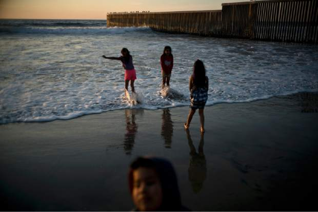 Children play at the beach near the border fence in Tijuana, Mexico, Sunday, Nov. 18, 2018. While many in Tijuana are sympathetic to the plight of Central American migrants and trying to assist, some locals have shouted insults, hurled rocks and even thrown punches at the migrants. (AP Photo/Ramon Espinosa)