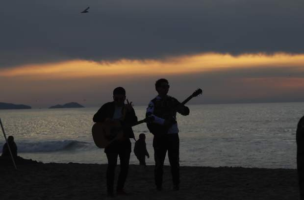 Musicians are silhouetted against Playa Tijuana, Mexico, Saturday, Nov. 17, 2018. Many of the nearly 3,000 migrants have reached the border with California. The mayor has called the migrants' arrival an