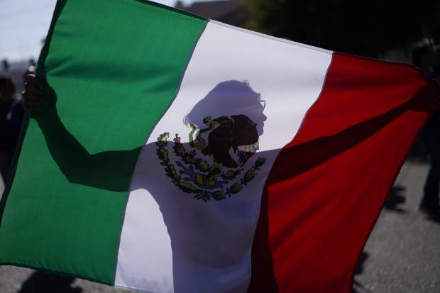 A demonstrator holds a Mexican flag outside a migrant shelter to protest the presence of thousands of Central American migrants in Tijuana, Mexico, Sunday, Nov. 18, 2018. Protesters accused the migrants of being messy, ungrateful and a danger to Tijuana; complained about how the caravan forced its way into Mexico, calling it an