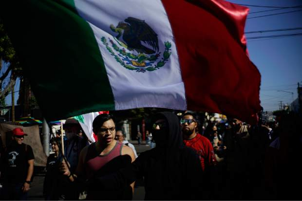 A demonstrator carries a Mexican flag during a protest against the presence of thousands of Central American migrants in Tijuana, Mexico, Sunday, Nov. 18, 2018. Protesters accused the migrants of being messy, ungrateful and a danger to Tijuana; complained about how the caravan forced its way into Mexico, calling it an