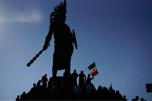 Demonstrators stand under an indigenous statue of Aztec ruler Cuauhtemoc as they protest the presence of thousands of Central American migrants in Tijuana, Mexico, Sunday, Nov. 18, 2018. Protesters accused the migrants of being messy, ungrateful and a danger to Tijuana; complained about how the caravan forced its way into Mexico, calling it an