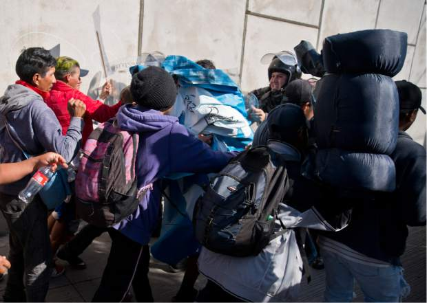 Migrants push past Mexican police at the Chaparral border crossing in Tijuana, Mexico, Sunday, Nov. 25, 2018, as they try to reach the U.S. The mayor of Tijuana has declared a humanitarian crisis in his border city and says that he has asked the United Nations for aid to deal with the approximately 5,000 Central American migrants who have arrived in the city. (AP Photo/Ramon Espinosa)