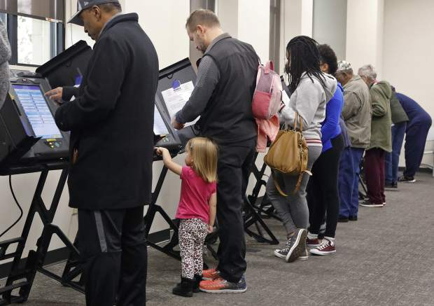Madelyn Whitehead, 2, helps her father, Rob Whitehead, from Maryland Heights, vote during absentee voting on Monday, Nov. 5, 2018, at the St. Louis County Board of Elections in St. Ann, Mo. (J.B. Forbes/St. Louis Post-Dispatch via AP)