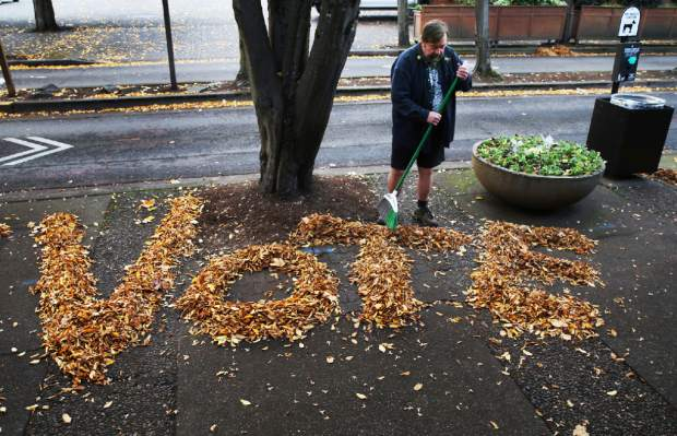 In this Nov. 4, 2018, photo Tim Boyden uses the loose fall leaves in front of his business Out On A Limb Gallery in Eugene, Ore., to encourage people passing by to vote in the midterm election. (Chris Pietsch/The Register-Guard via AP)