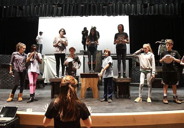 """Jennetta Howell, co-director, talks casts members through a scene during the first full rehearsal of the Defiance Community Players production of """"Oliver"""" on the stage in Jeannie Miller Theatre at Glenwood Springs High School Monday. After a two-year absence Defiance is set to open its latest production Nov. 9 at 7 p.m."""