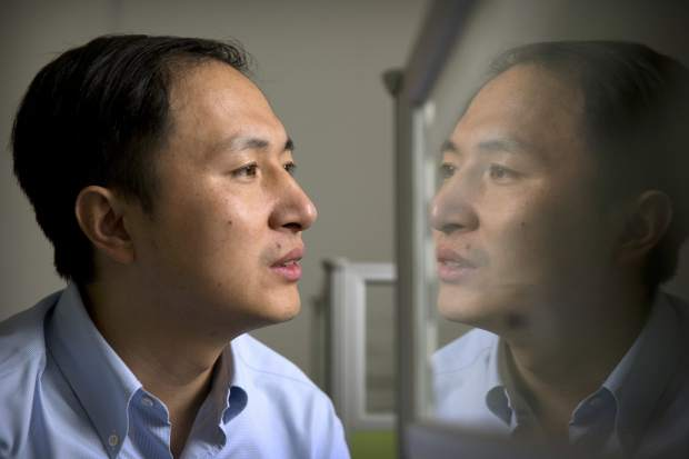 In this Oct. 10, 2018 photo, He Jiankui is reflected in a glass panel as he works at a computer at a laboratory in Shenzhen in southern China's Guangdong province. Chinese scientist He claims he helped make world's first genetically edited babies: twin girls whose DNA he said he altered. He revealed it Monday, Nov. 26, in Hong Kong to one of the organizers of an international conference on gene editing. (AP Photo/Mark Schiefelbein)