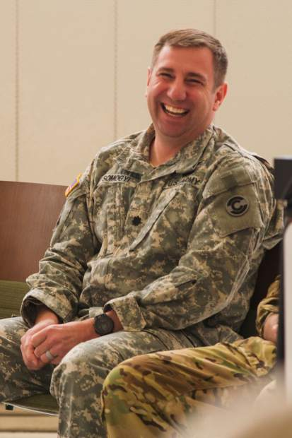 Lt. Col. Anthony Somogyi enjoys a laugh during his retirement ceremony among a group of military and local officials as well as HAATs troops in the helicopter bay in Gypsum.
