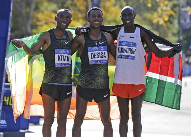 Second place finisher Shura Kitata of Ethiopia, left, first place finisher Lelisa Desisa of Ethiopia, center, and third place finisher Geoffrey Kamworor of Kenya pose for a picture at the finish line of the New York City Marathon in New York, Sunday, Nov. 4, 2018. (AP Photo/Seth Wenig)