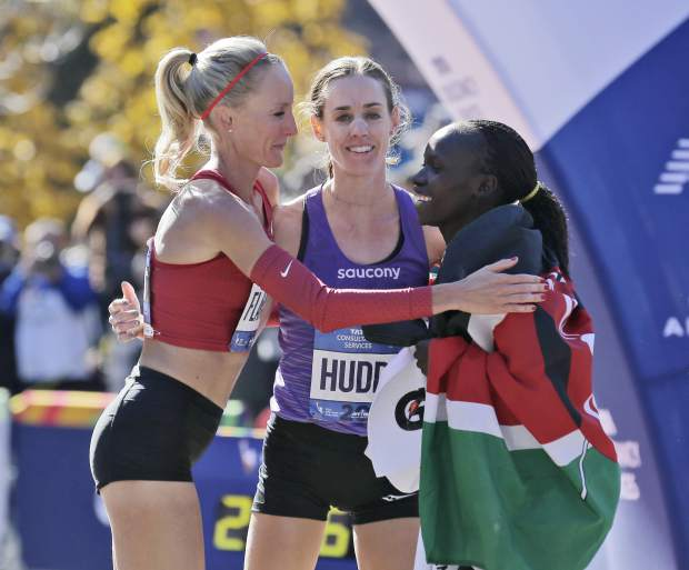 First place finisher Mary Keitany of Kenya, right, greets American runners Shalane Flanagan, left, and Molly Huddle at the finish line of the New York City Marathon in New York, Sunday, Nov. 4, 2018. (AP Photo/Seth Wenig)