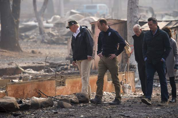 President Donald Trump, from left, FEMA Administrator Brock Long, California Gov. Jerry Brown, Gov.-elect Gavin Newsom and Paradise Mayor Jody Jones tour the Skyway Villa Mobile Home and RV Park during Trump's visit of the Camp Fire in Paradise, Calif., Saturday, Nov. 17, 2018. Trump went to Northern California on Saturday to survey the devastation from the nation's deadliest wildfire in a century. (Paul Kitagaki Jr./The Sacramento Bee via AP, Pool)