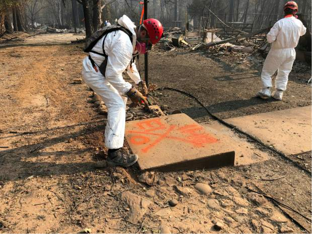 A volunteer member of an El Dorado County search and rescue team uses orange spray paint to mark the ruins of a home to show that no human remains were found at the location in Paradise, Calif., Sunday, Nov. 18, 2018, following a Northern California wildfire. (AP Photo/Sudhin Thanawala)
