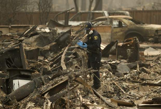 FILE - In this Thursday, Nov. 15, 2018 file photo, a Sheriff's deputy looks for human remains at a home burned in the Camp fire in Magalia, Calif. Searchers are in a race against time with long-awaited rains expected in the Northern California fire zone where dozens of bodies have been recovered so far. While the rain is good for tamping down the still-burning fire, it will turn the fire zone into a muddy mess and make it more difficult for crews to search. (AP Photo/John Locher, File)