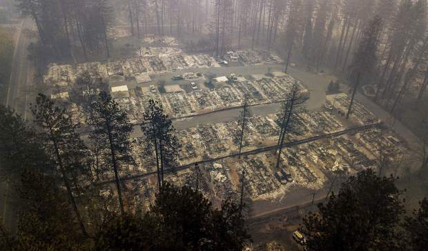 FILE - In this Thursday, Nov. 15, 2018, file photo, residences leveled by the wildfire line a neighborhood in Paradise, Calif. Northern California crews battling the country's deadliest wildfire in a century were bracing for strong winds Sunday, Nov. 18, that could erode gains they have made in containing the fearsome blaze, which has killed dozens and leveled a town. (AP Photo/Noah Berger, File)