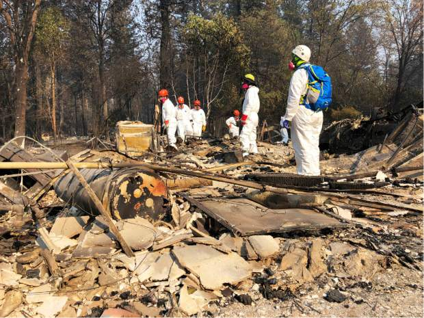 Volunteer members of an El Dorado County search and rescue team search the ruins of a home, looking for human remains, in Paradise, Calif., Sunday, Nov. 18, 2018, following a Northern California wildfire. (AP Photo/Sudhin Thanawala)