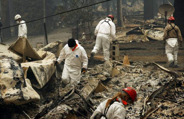 FILE - In this Tuesday, Nov. 13, 2018 file photo, search and rescue workers search for human remains at a trailer park burned out from the Camp fire in Paradise, Calif. Searchers are in a race against time with long-awaited rains expected in the Northern California fire zone where dozens of bodies have been recovered so far. While the rain is good for tamping down the still-burning fire, it will turn the fire zone into a muddy mess and make it more difficult for crews to search. (AP Photo/John Locher, File)