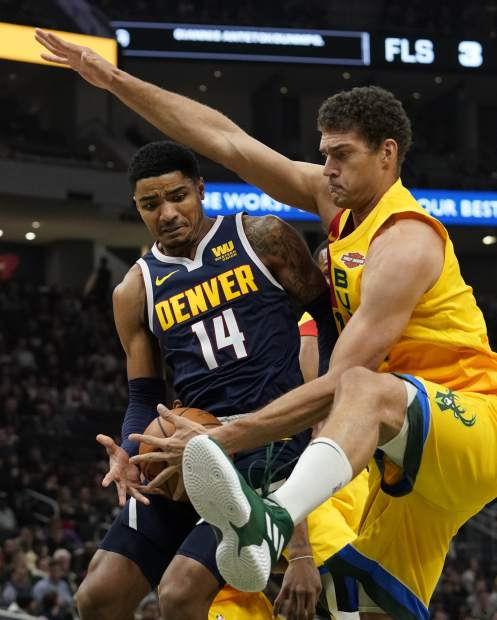 Denver Nuggets' Gary Harris and Milwaukee Bucks' Brook Lopez go after a loose ball during the first half of an NBA basketball game Monday, Nov. 19, 2018, in Milwaukee. (AP Photo/Morry Gash)