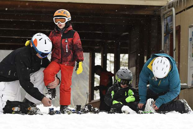 Edwin Pipers, left, and Emily Pipers, far right, help their sons Clark, 6, and Charlie 3, gear up for the first run of the season Friday at Sunlight Mountain Resort. Sunlight celebrated its 52nd season with one of the resort's earliest openings on record.