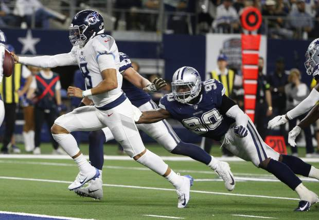 Tennessee Titans quarterback Marcus Mariota (8) runs for a touchdown against Dallas Cowboys defensive end Demarcus Lawrence (90) during the second half of an NFL football game, Monday, Nov. 5, 2018, in Arlington, Texas. (AP Photo/Michael Ainsworth)