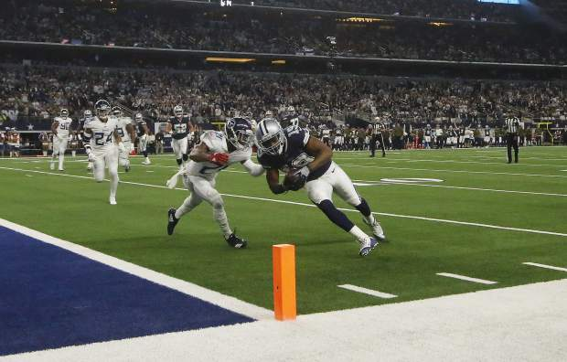 Dallas Cowboys wide receiver Amari Cooper (19) runs into the end zone as Tennessee Titans cornerback Malcolm Butler (21) defends during the first half of an NFL football game, Monday, Nov. 5, 2018, in Arlington, Texas. (AP Photo/Michael Ainsworth)