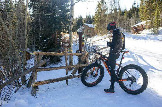 A local fat-tire cyclist, Taylor Shelden, check his cellphone after discovering the news of Wellington Trail being closed at the trailhead on Thursday, Nov. 15, in Breckenridge.