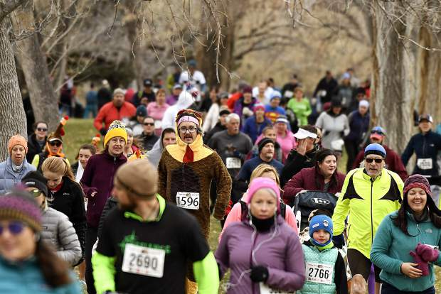 Bundled up runners, including a turkey costume-clad trotter, wind their way through the trees for the 33rd annual Turkey Day 5K Thursday morning at the Glenwood Springs Golf Course.