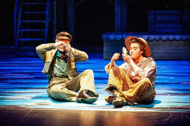 Curtis Madden playing Tom Sawyer and Patrick Kelehen smoke pipes in a scene from the Aspen Community Theatre dress rehearsal of the musical