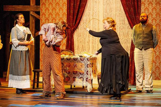 Patrick Keleher playing Huck Finn getting whipped by Widow Douglas, played by Lynette Schlepp in a scene from the Aspen Community Theatre dress rehearsal of the musical