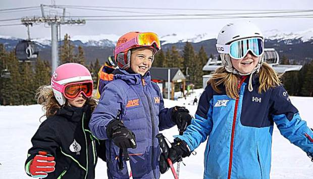 3 AVSC girls laugh at the top of Aspen Mountain for opening day on Saturday.