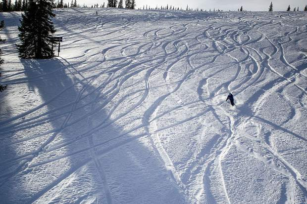 A skier makes some turns through the powder under the Big Burn Lift at Snowmass for opening day Thursday.