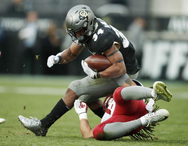 Washington State linebacker Jahad Woods, bottom, pulls down Colorado running back Travon McMillian after a short gain in the second half of an NCAA college football game Saturday, Nov. 10, 2018, in Boulder, Colo. Washington State won 31-7. (AP Photo/David Zalubowski)